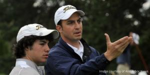 Coach helping high school golfer